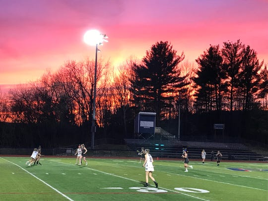 A spectacular sunset provides a backdrop for Chenango Forks' Section 4 Conference girls lacrosse game against visiting Owego on Monday. The Blue Devils won, 8-7.