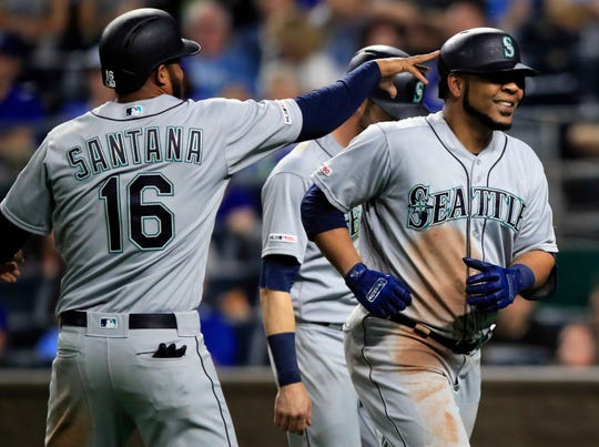 Seattle Mariners' Edwin Encarnacion, right, is congratulated by teammate Domingo Santana (16) after his three-run home run during the sixth inning of a baseball game against the Kansas City Royals at Kauffman Stadium in Kansas City, Mo., Monday, April 8, 2019. It was the second home run of the inning for Encarnacion.