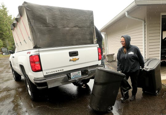 Tammy Stein wheels the bins to her brother Daniel's truck as they collect trash from one of their clients in Seabeck on Friday, April 5, 2019.