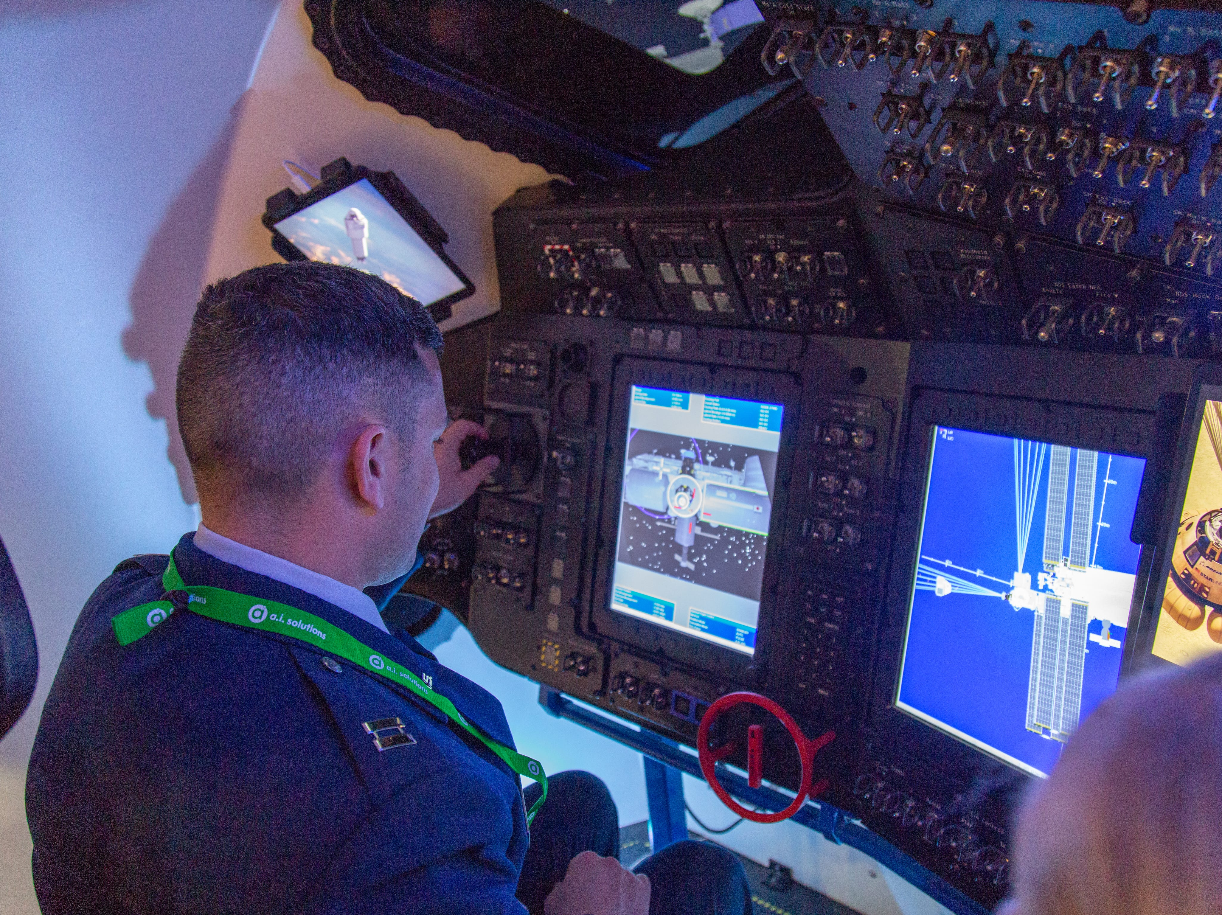 An Air Force captain uses the Starliner simulator in Boeing's exhibit during the 35th Space Symposium in Colorado Springs on Monday, April 8, 2019.