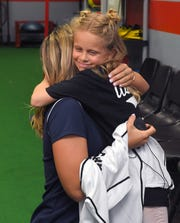 """Brookelynn Dolin, 10, gets a warm hug from pro softball star Alex Powers, who called their meeting """"a humbling experience."""""""