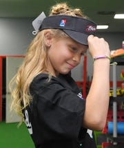 Brookelynn Dolin, 10, tries on a USSSA Pride visor given to her by her favorite pro softball player, Alex Powers.