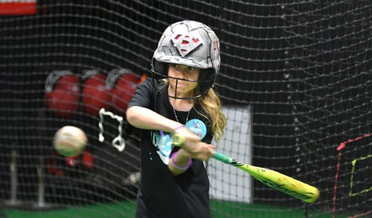 Brookelynn Dolin, 10, takes her first swings in a batting cage during the day she spent with pro softball star Alex Powers, a meeting set up by the Kids Wish Network of Florida.