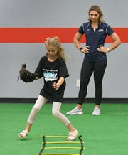 """Pro softball star Alex Powers watches as Brookelynn Dolin, 10, runs some """"ladder"""" drills at the Upper Deck Sports Facility in Suntree."""