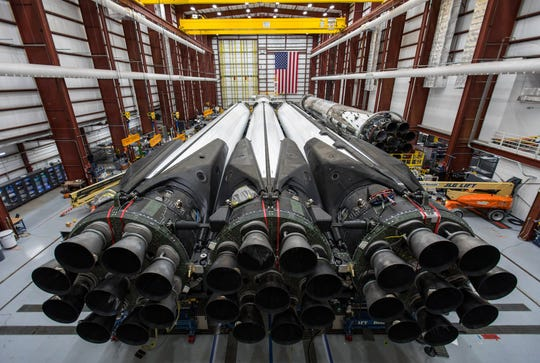 In a Kennedy Space Center hangar, 27 main engines are visible at the base of three boosters making up the first stage of SpaceX's Falcon Heavy rocket, which is being prepared to lift the Arabsat-6A communications satellite into orbit.