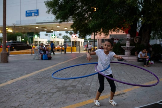 A young migrant girl plays with a hula hoop in a makeshift camp at the next to the international bridge in Matamoros, Mexico where migrants wait for weeks to seek asylum in the U.S on Thursday, April 4, 2019.