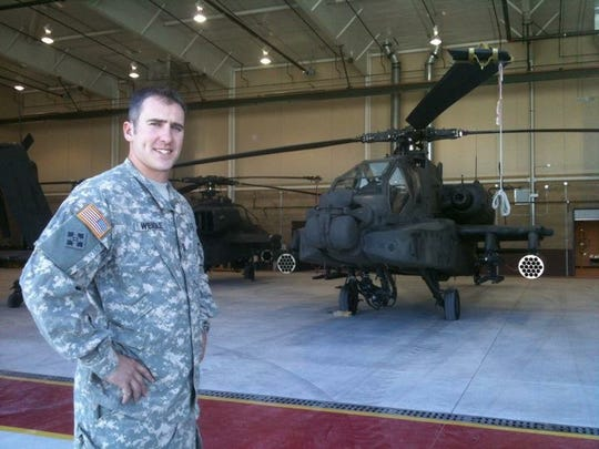 Hooks general manager Wes Weigle poses next to an Apache helicopter during his time in the Army.