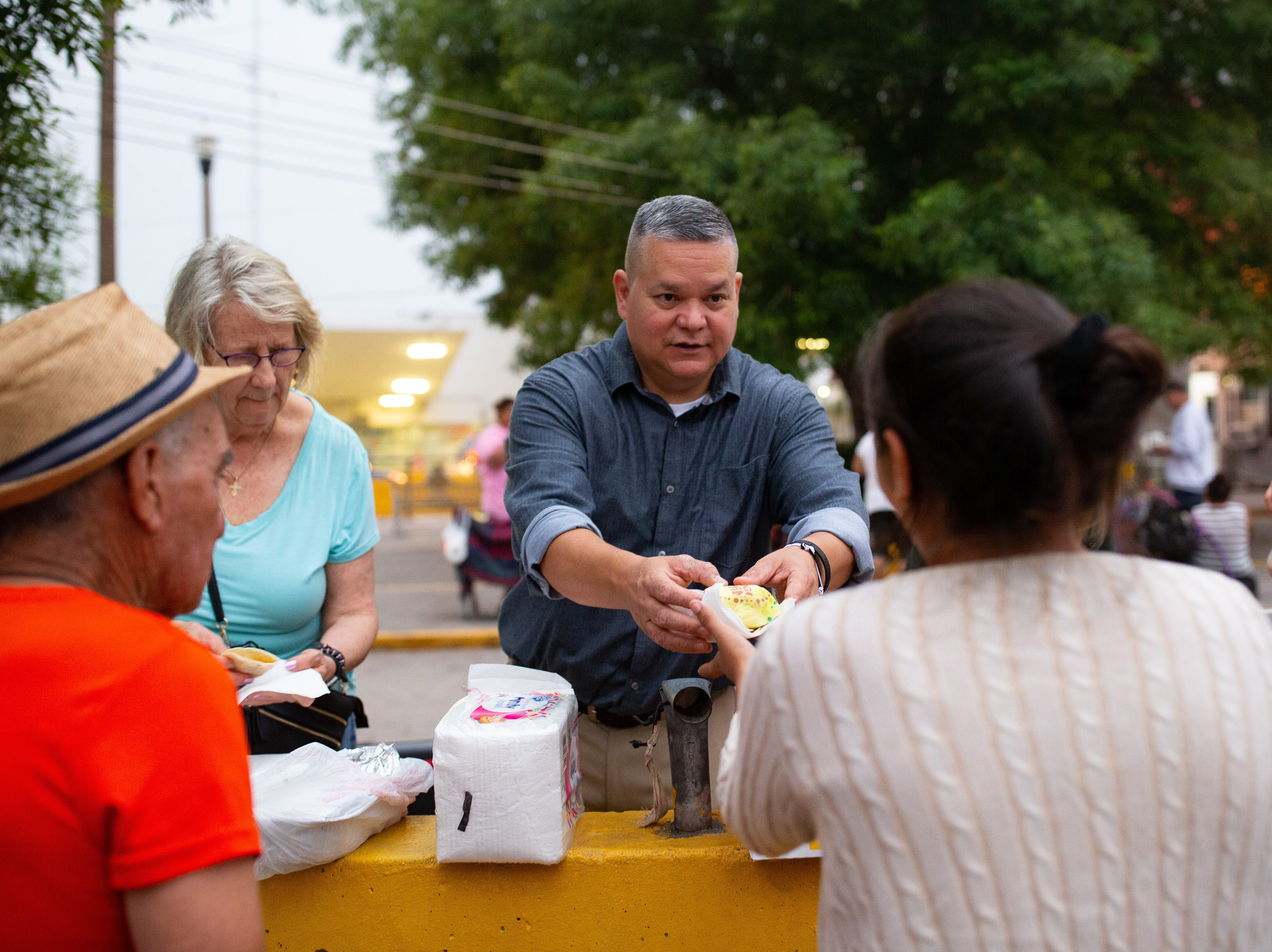 Mike Benavides, of Team Brownsville and Ann Finch of Austin feed migrants breakfast on the Matamoros Mexico side of the Gateway International Bridge on Friday, April 5, 2019. Mike Benavides and other volunteers bring two meals a day from the Brownsville Texas to Matamoros Mexico to help the migrants waiting to seek asylum in the US.