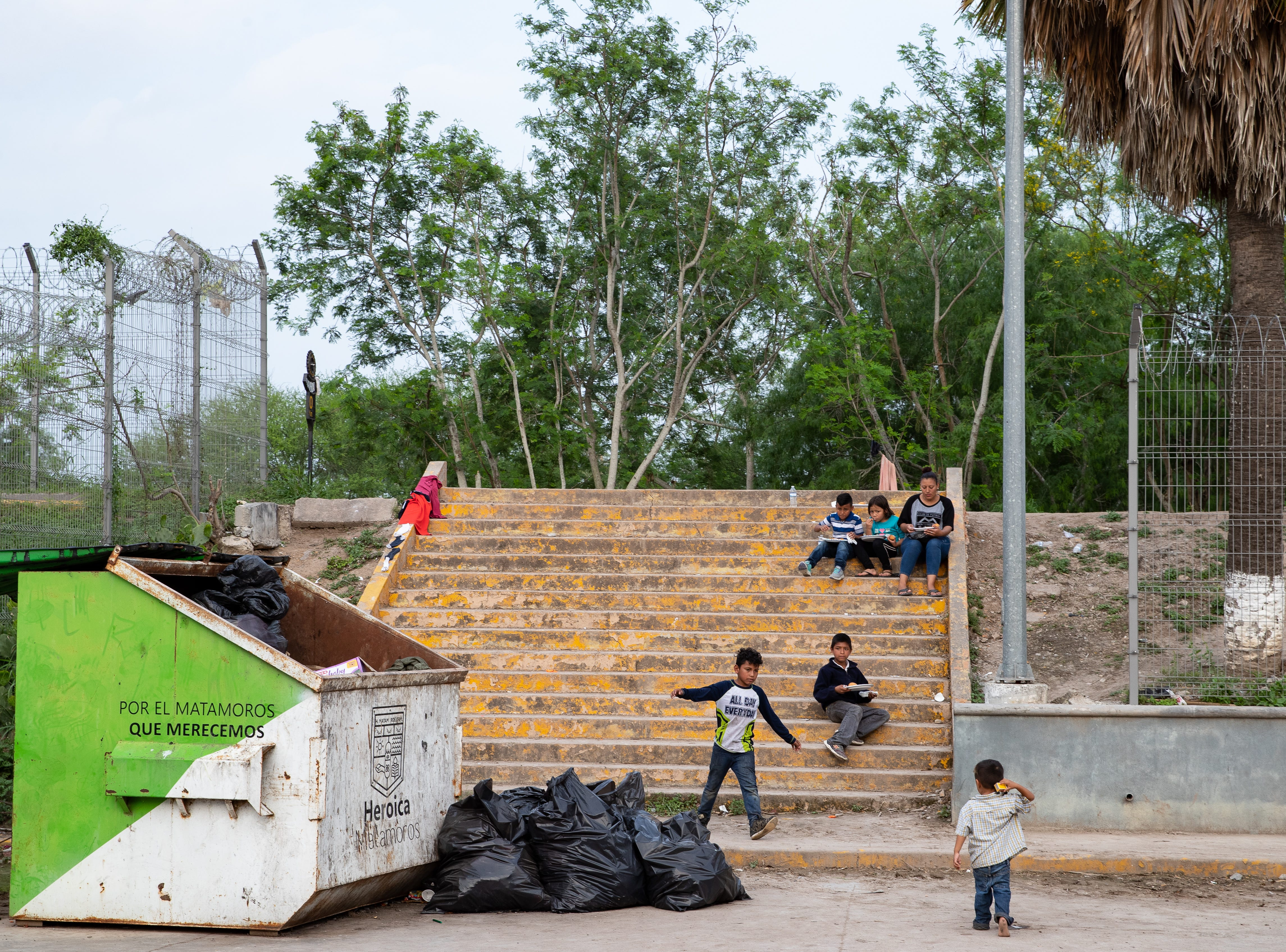 A group of Central American migrants on Thursday, April 4, 2019, waiting to seek asylum in the U.S  eat their dinner from Team Brownsville on steps near  the Matamoros Toll Plaza in Mexico where many of them have been camped out for weeks.