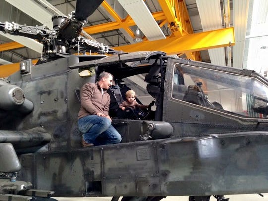 Hooks general manager Wes Weigle sits on the side of an Apache helicopter as one of his sons sits in the seat. Weigle flew Apaches during his nearly nine-year stint in the Army.