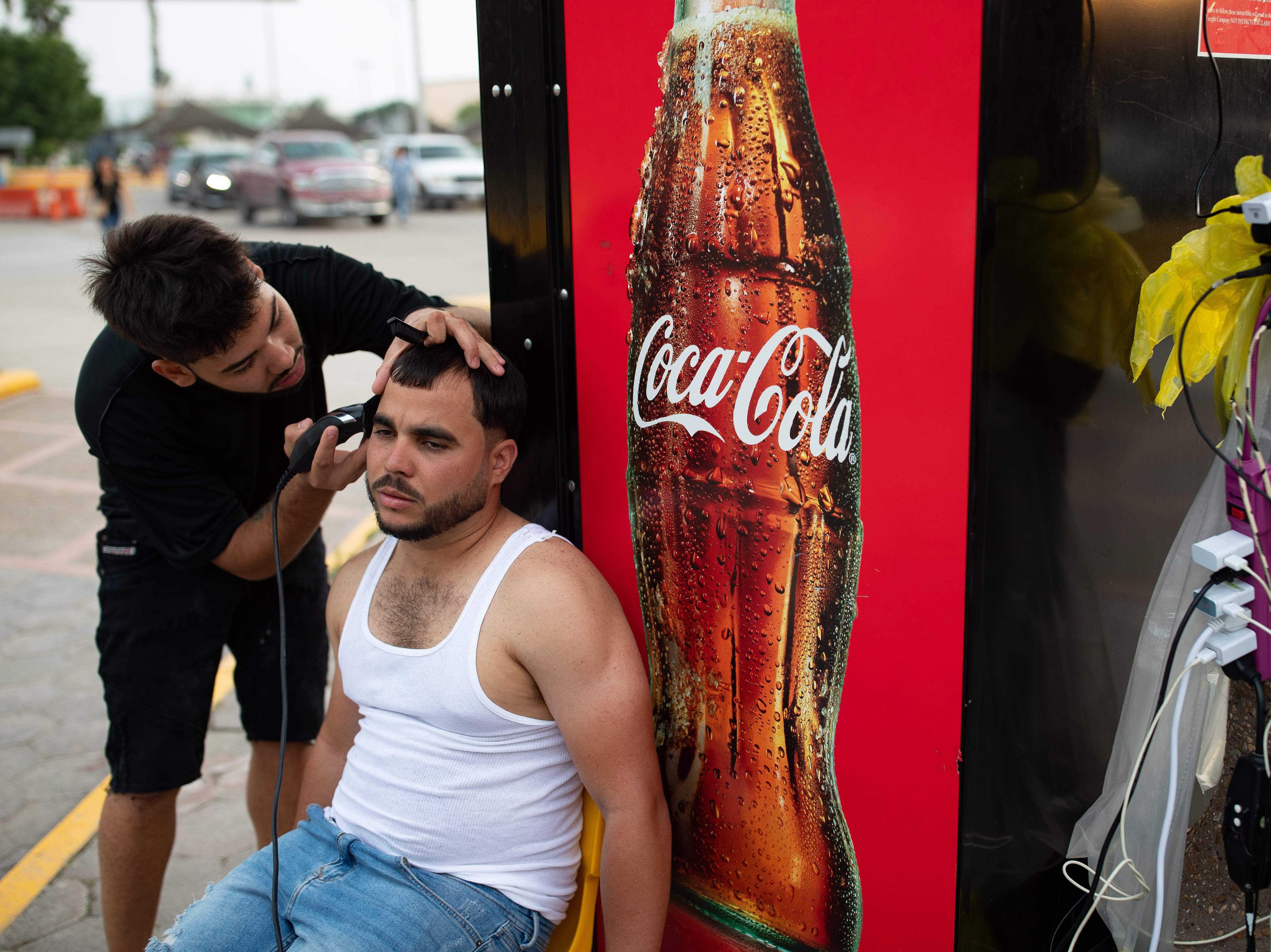 Central American migrants cut each others' hair using power from a light post as they wait to seek asylum in the U.S in a makeshift camp next to the international bridge in Matamoros, Mexico on Thursday, April 4, 2019.