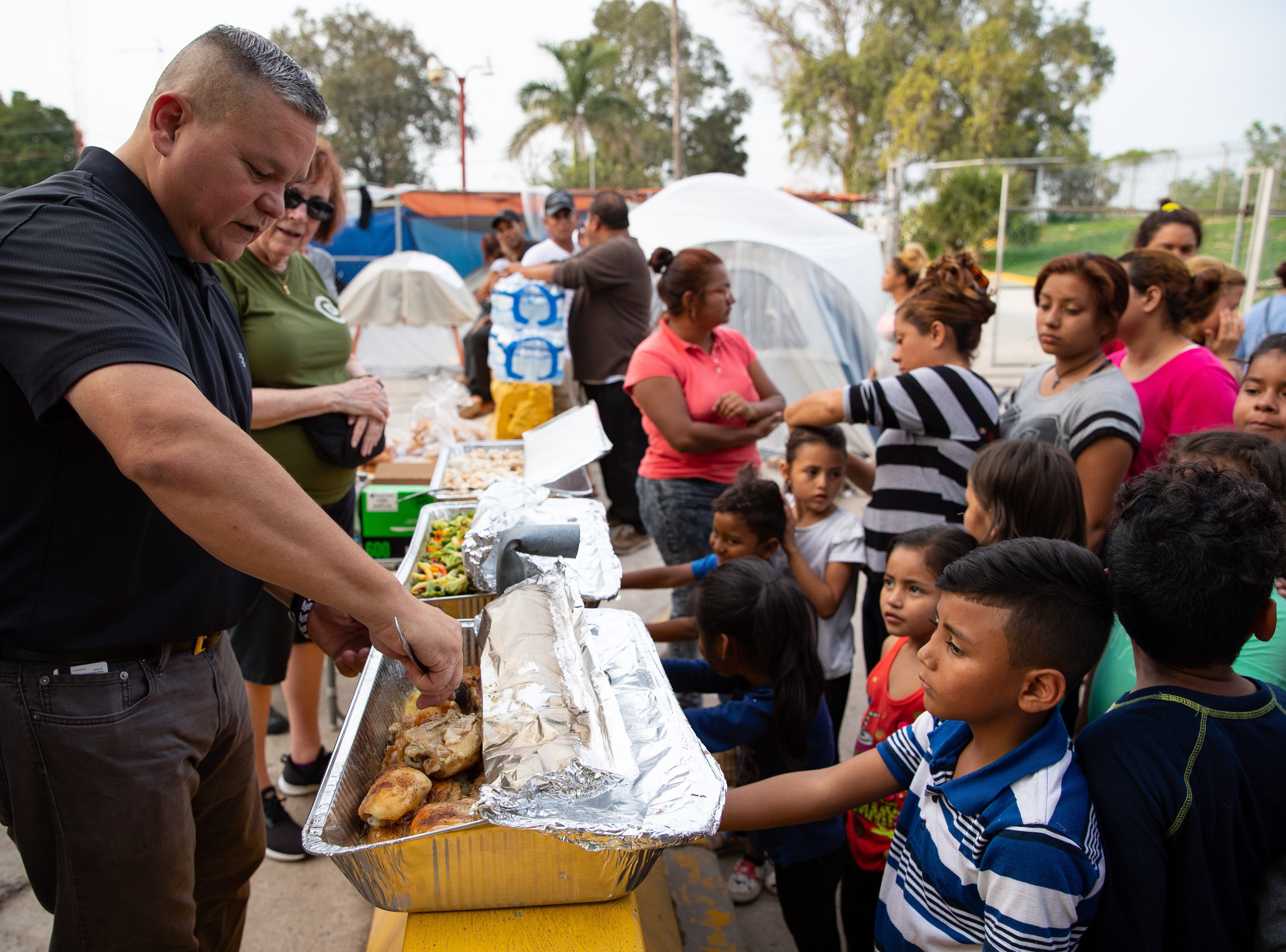 Mike Benavides, of Team Brownsville, and a group of volunteers serve dinner to migrants waiting to seek asylum in the U.S who are camped out in a park next to the the international bridge in Matamoros, Mexico on Thursday, April 4, 2019. Benavides and other volunteers bring two meals a day from the Brownsville Texas to Matamoros, Mexico to help the migrants waiting to seek asylum in the US.