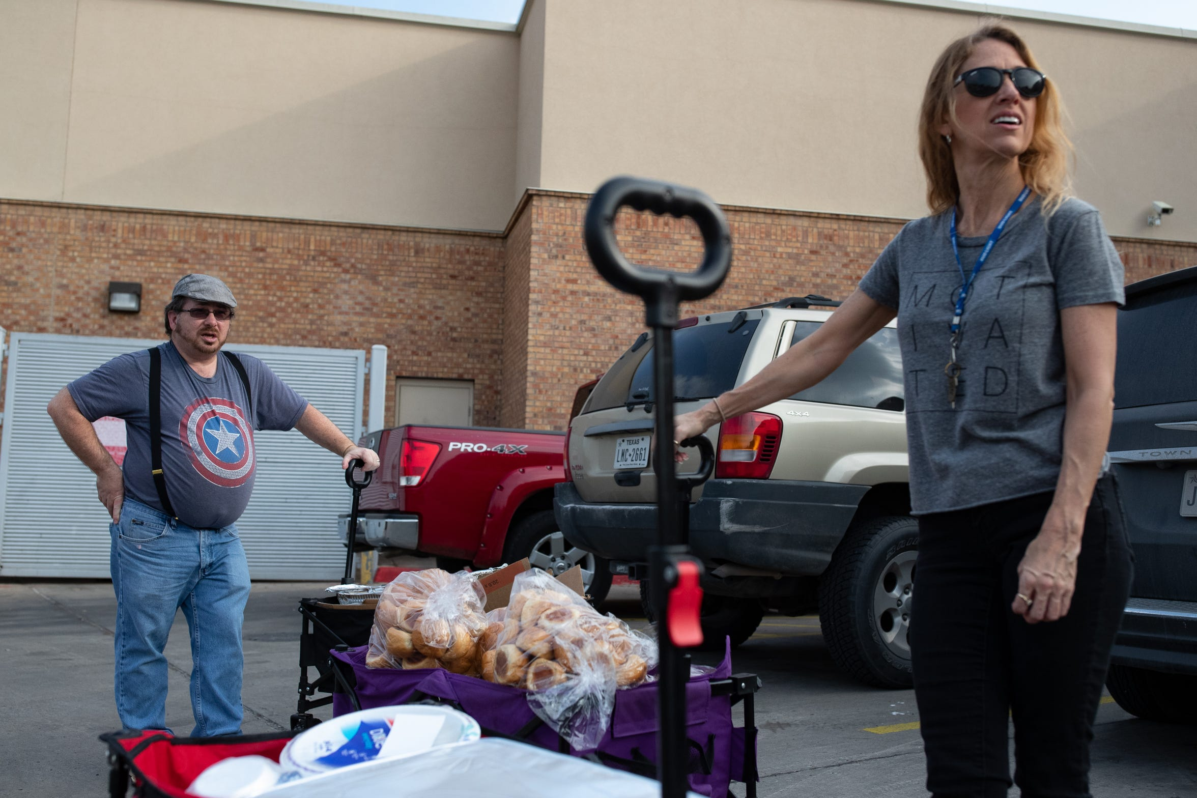 Volunteers Emmett Blake and Diane Beckman of Austin, stand outside the Brownsville bus station with carts full of food before Team Brownsville's dinner and supply run over the Gateway International Bridge to help migrants waiting to seek asylum camped out in Matamoros, Mexico on Thursday, April 4, 2019.