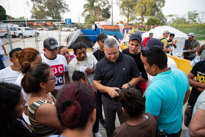 Mike Benavides, of Team Brownsville, makes a list of supplies need as he talks to migrants waiting to asylum in the U.S camped out next to the international bridge in Matamoros, Mexico  on Thursday, April 4, 2019.  Benavides and other volunteers bring two meals a day and supplies from Brownsville, Texas to Matamoros, Mexico to help the migrants.