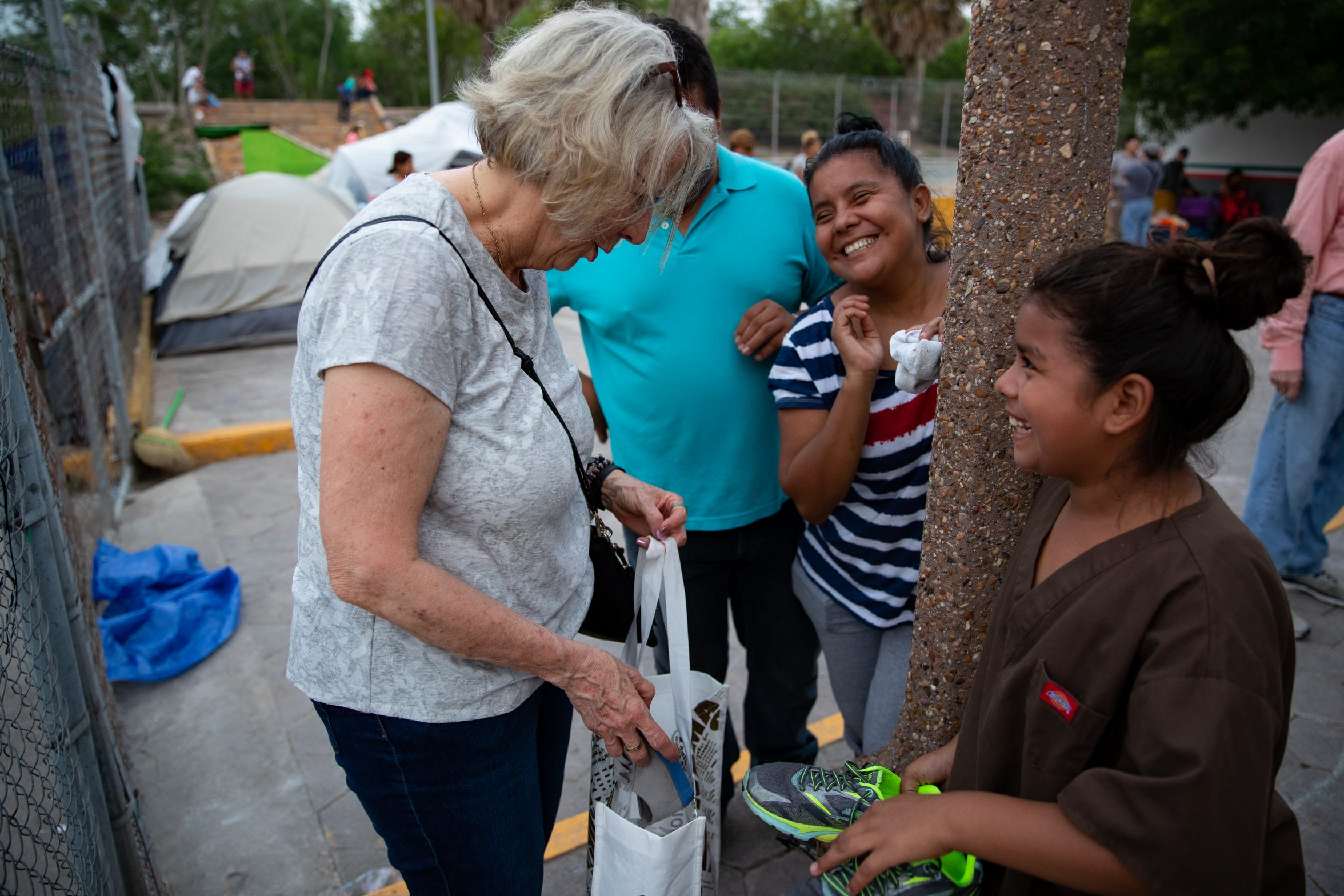 Ann Finch of Austin, Texas, hands a young migrant girl a pair of shoes as she stays in a makeshift camp next to the international bridge in Matamoros, Mexico waiting to seek asylum in the U.S on Thursday, April 4, 2019.
