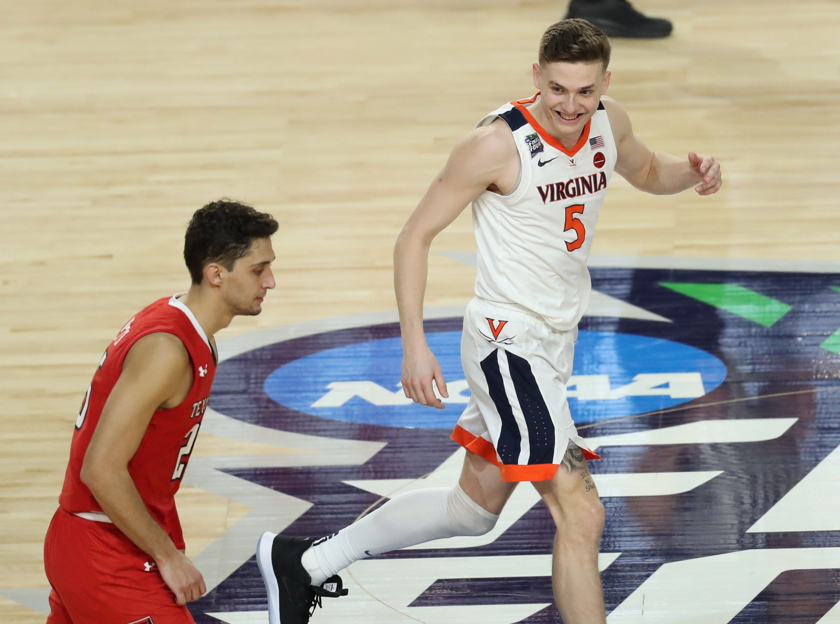 Apr 8, 2019; Minneapolis, MN, USA; Virginia Cavaliers guard Kyle Guy (5) smiles as he runs down the court with Texas Tech Red Raiders guard Davide Moretti (25) during the second half in the championship game of the 2019 men's Final Four at US Bank Stadium. Mandatory Credit: Brace Hemmelgarn-USA TODAY Sports