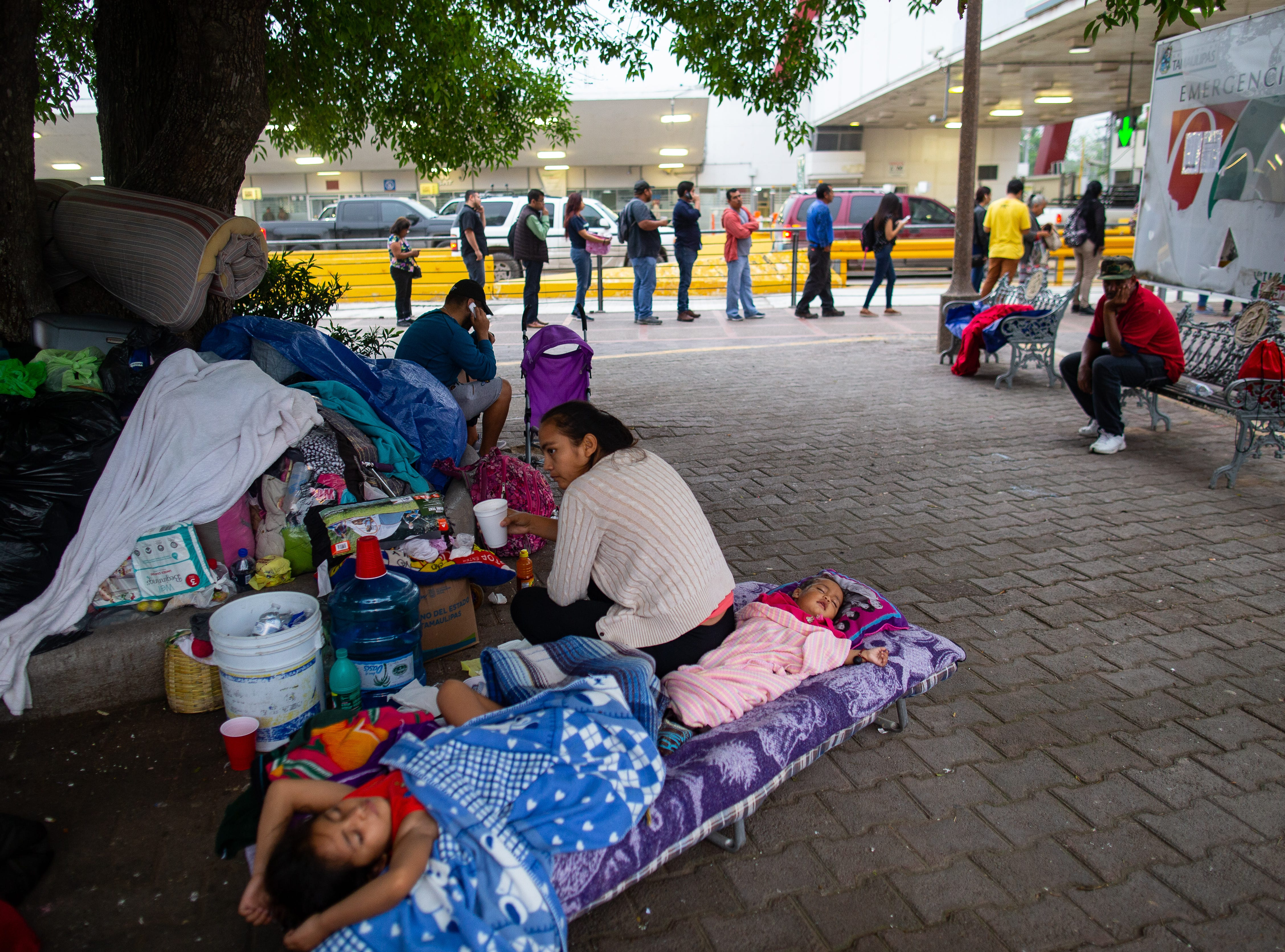 Migrants from El Salvador including 7-month old Violet and 6-year-old Joanna sleep on a cot in a makeshift camp on the Matamoros Mexico side of the Gateway International Bridge as their families wait to apply for asylum in the U.S. on Friday, April 5, 2019.