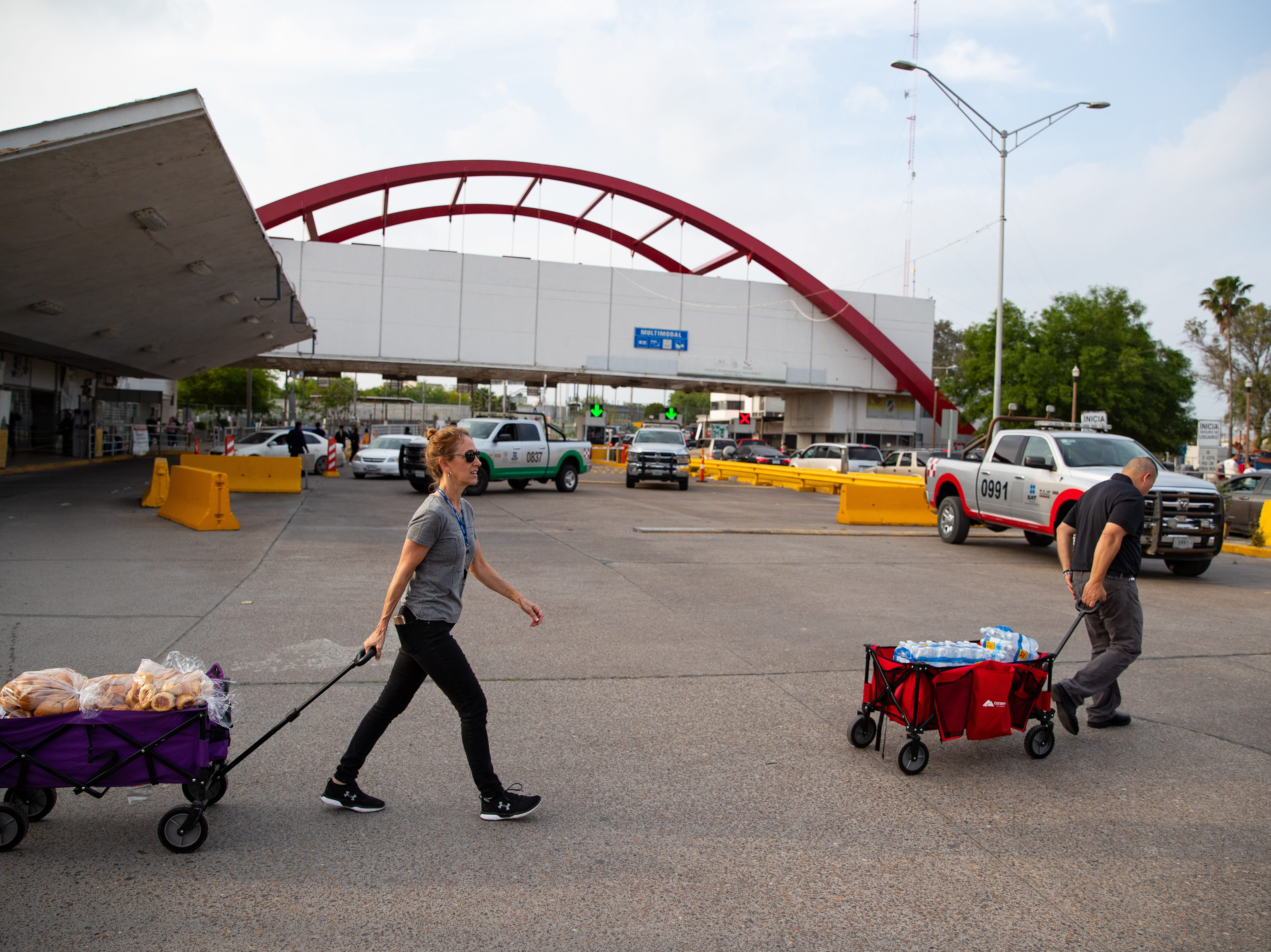 Mike Benavides, of Team Brownsville, and Diane Beckman of Austin, Texas, pull carts full of food and supplies across the road to feed dinner to a group of migrants waiting to seek asylum in the U.S camped out in a park next to the international bridge in Matamoros, Mexico on Thursday, April 4, 2019.