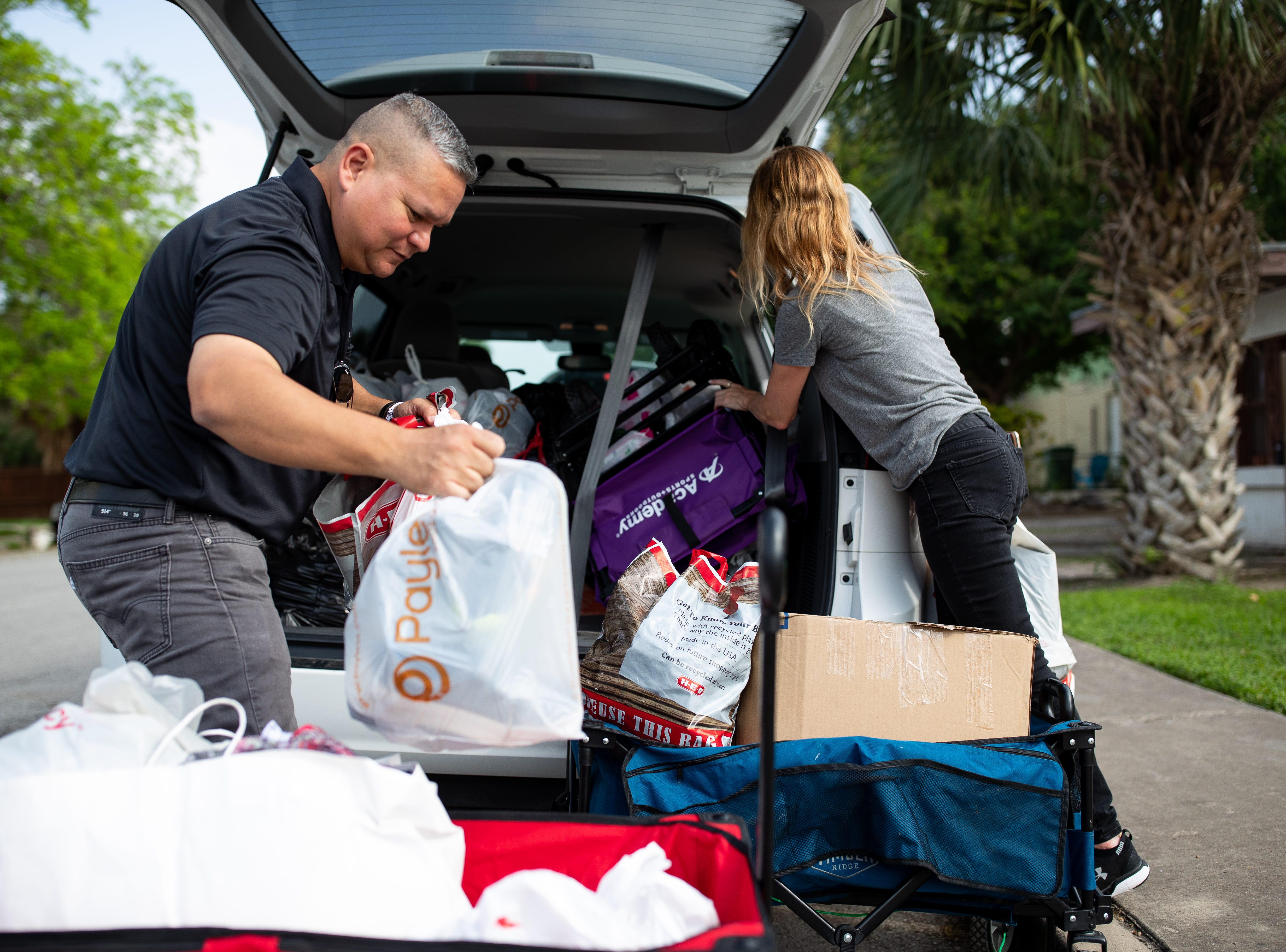 Mike Benavides, of Team Brownsville, helps Diane Beckman of Austin, unload a car full of supplies to help migrants she and two others drove down to Brownsville from Austin in on Thursday, April 4, 2019. Benavides and other volunteers bring two meals a day from Brownsville, Texas to Matamoros, Mexico to help the migrants waiting to seek asylum in the US.