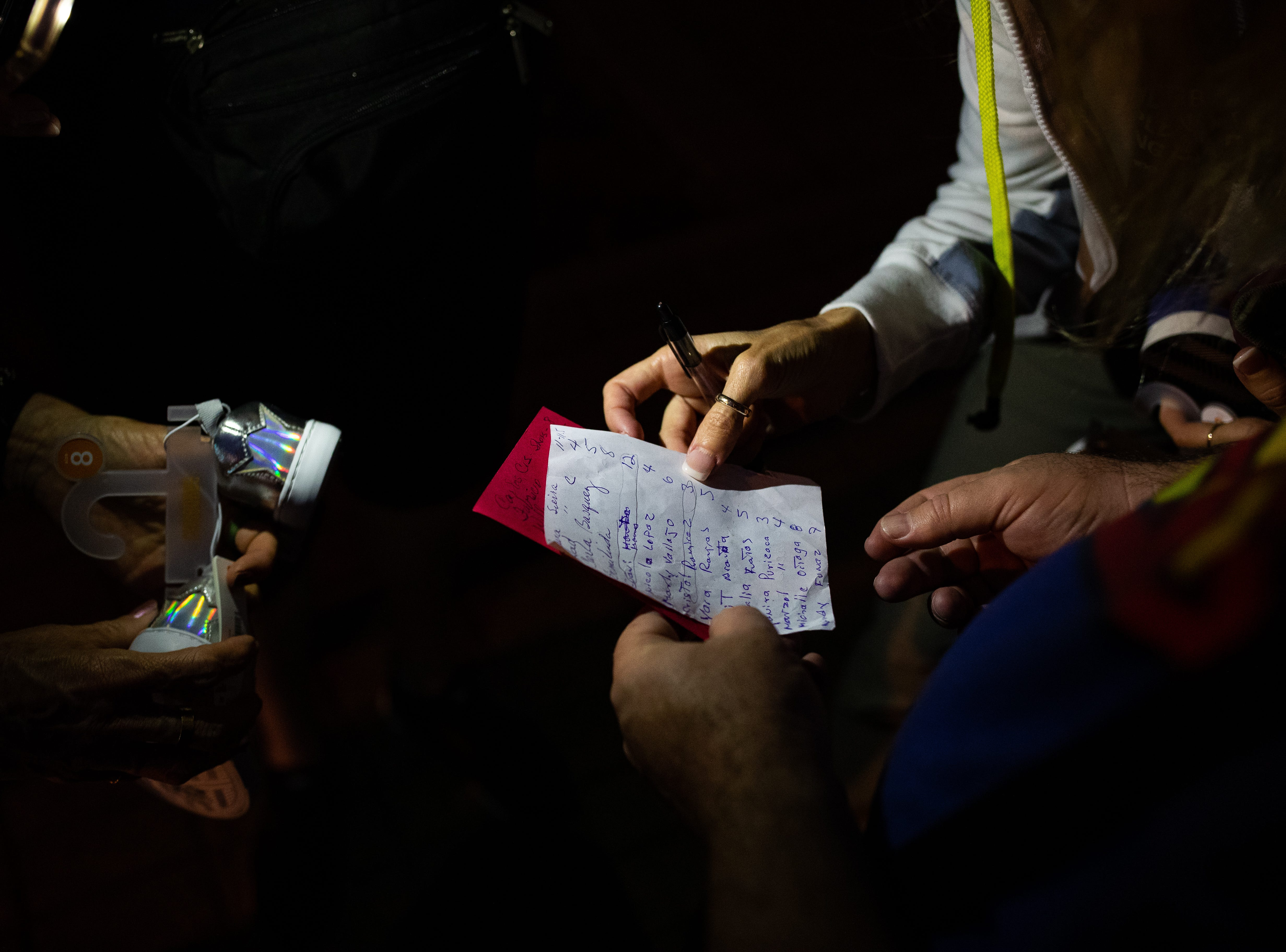 Team Brownsville volunteers Emmett Blake, Diane Beckman, Anne Rioux and Ann Finch of Austin use a cellphone light to read a list of shoes sizes needed for migrants before crossing the Gateway International Bridge to serve breakfast  in Matamoros Mexico on Friday, April 5, 2019.