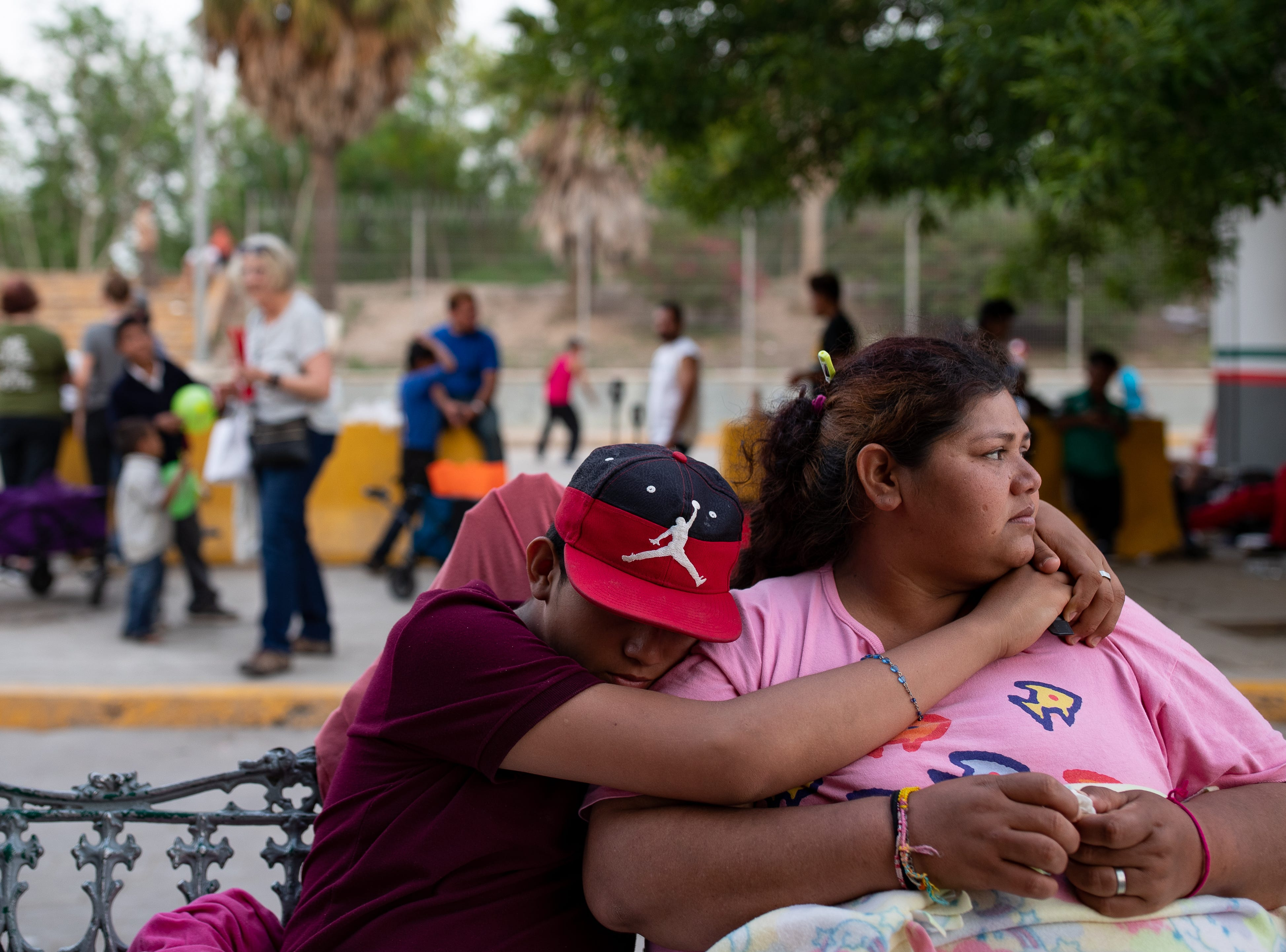 Jeffrey Sierra holds on to his mom Laura Soto on Thursday, April 4, 2019 as they sit in a makeshift camp next to the international bridge in Matamoros, Mexico where migrants wait for weeks to seek asylum in the U.S. The pair came from Honduras.