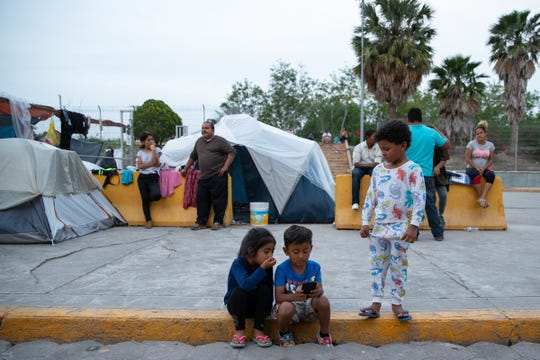 Three migrant children play on a cellphone in a makeshift camp next to the international bridge in Matamoros, Mexico as they wait with family members to seek asylum in the U.S on Thursday, April 4, 2019.