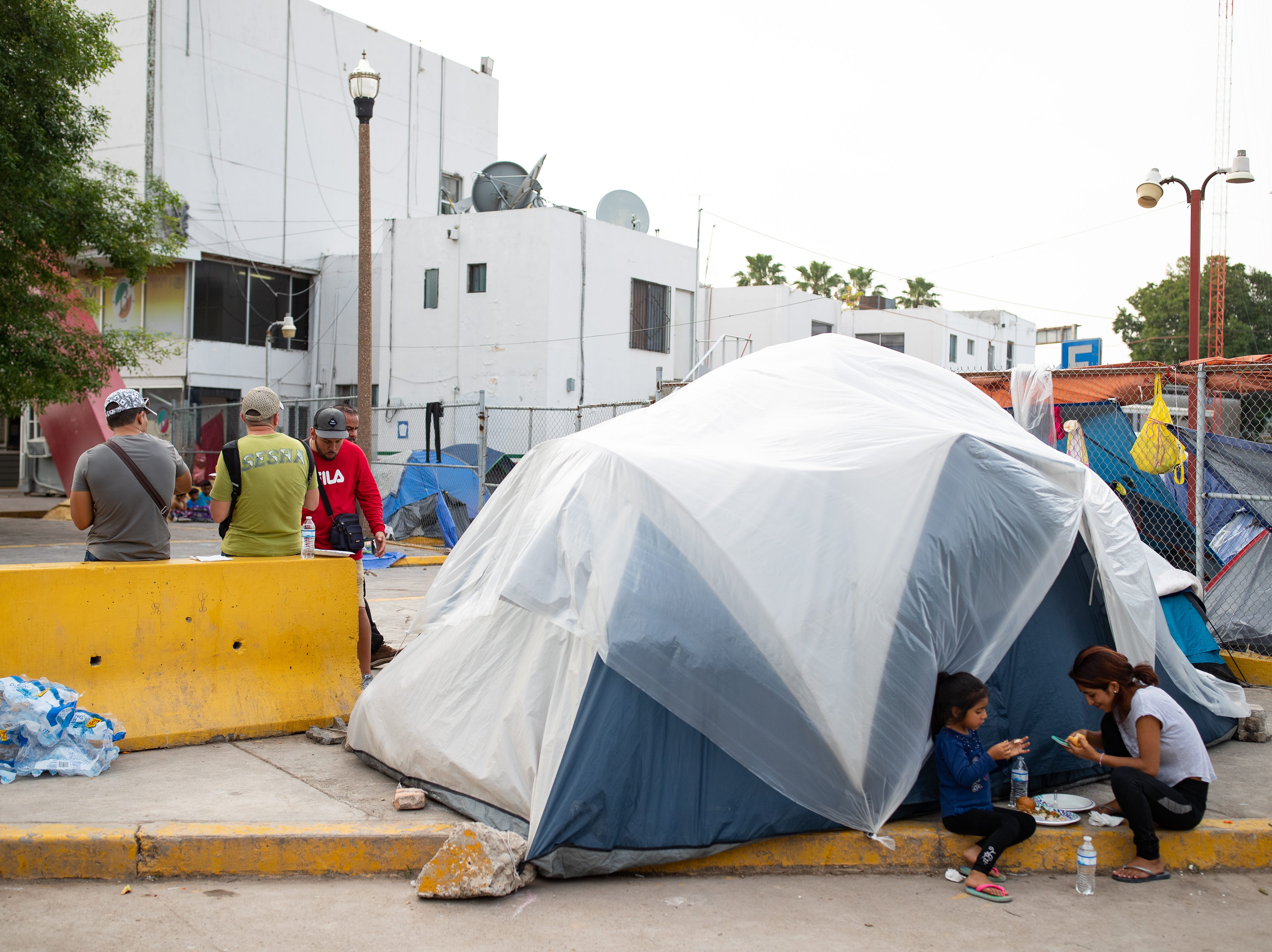 A migrant woman and a young girl eat their dinner next to their tent near the international bridge in Matamoros, Mexico along with other Central American migrants on Thursday, April 4, 2019, waiting in Mexico to seek asylum in the U.S.