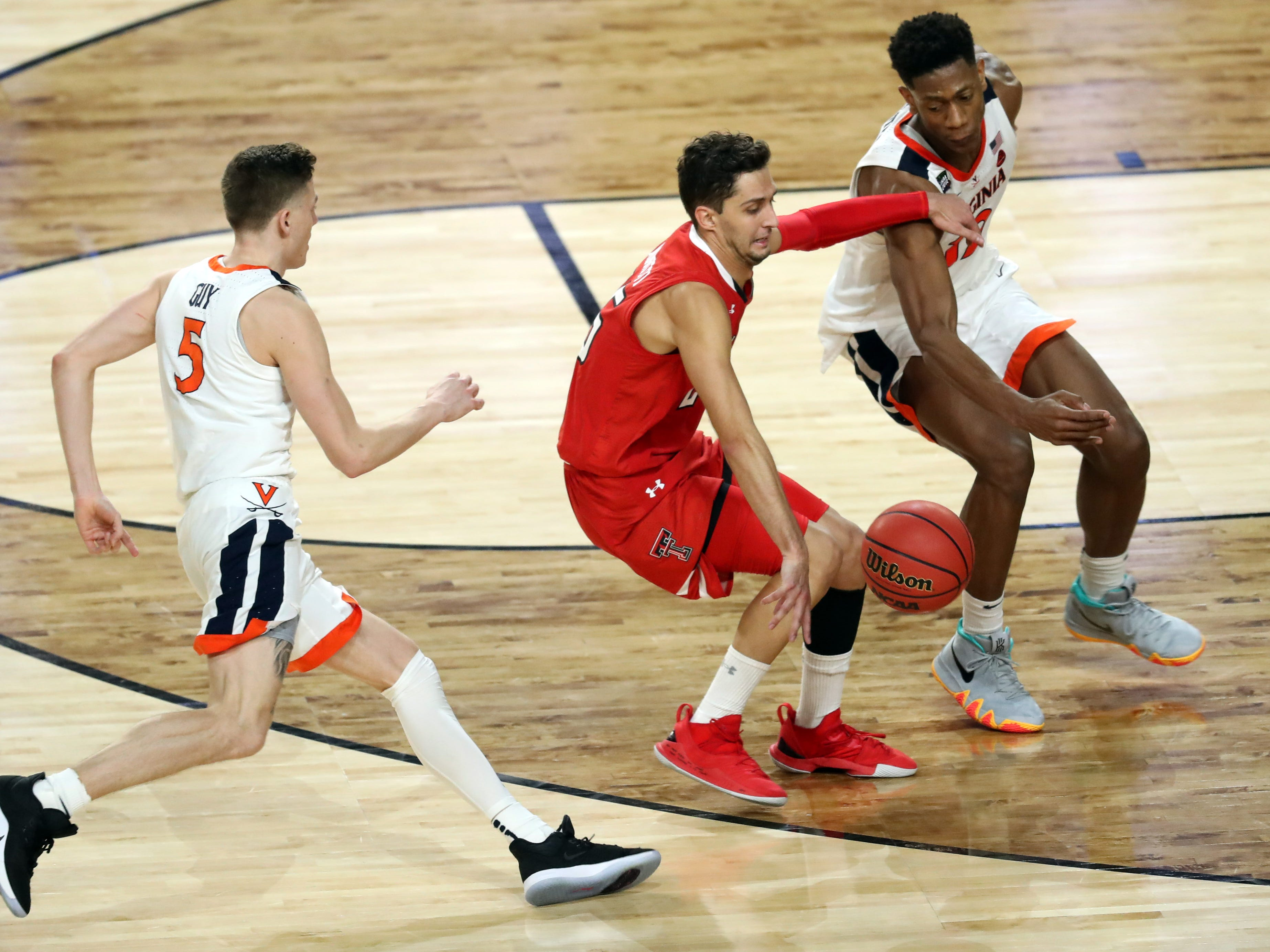 Apr 8, 2019; Minneapolis, MN, USA; Texas Tech Red Raiders guard Davide Moretti (25) drives the ball up the court while pressured by Virginia Cavaliers guard De'Andre Hunter (12) and guard Kyle Guy (5) during the second half in the championship game of the 2019 men's Final Four at US Bank Stadium. Mandatory Credit: Brace Hemmelgarn-USA TODAY Sports