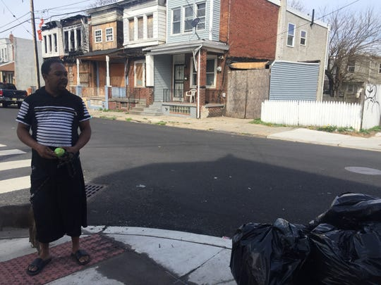 "Dontay Benson points to a pile of trash on Sheridan Street in Camden's Whitman Park neighborhood. He lives on Pulaski Street and said that residents keep their homes clean and properly dispose of trash; outsiders dump piles of refuse that draw vermin. ""You go to sleep and it's clean; you wake up and this is here,"" he said."