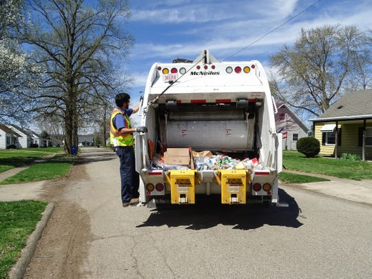 Chillicothe recycling crew member Ryan Owen rides on the back of the Chillicothe recycling truck during an afternoon route. Owen says that while the community is doing a great job, more education is needed.