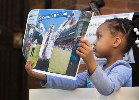 Kalei Rogers, 4, holds up a sign during a press conference on Tuesday, April 9, 2019, hosted by Fight Back Cincinnati: Wade street and Central Avenue Tenants United. The new group is fighting displacement for residents around the area near the new FC Cincinnati stadium in the West End. Rogers' family is facing displacement.