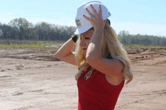 Christian County Chamber of Commerce CEO and President Kelli Pendleton tries on her hard hat at the groundbreaking of the multimillion-dollar Oak Grove Racing & Gaming venue on April 9, 2019.