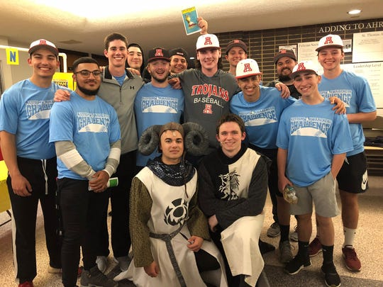 "Kevin O'Neil (kneeling right) and Ryan Breyta (kneeling left) are surrounded by Bishop Ahr baseball teammates following Saturday's high school performance of ""Spamalot."""