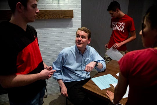 U.S. Sen. Michael Bennet, D-Colo, talks with a group of high school students from Urbandale after giving a speech and answering questions on Monday, April 8, 2019, during a meet and greet hosted by the Polk County Democrats at Teddy Maroon's in Des Moines.
