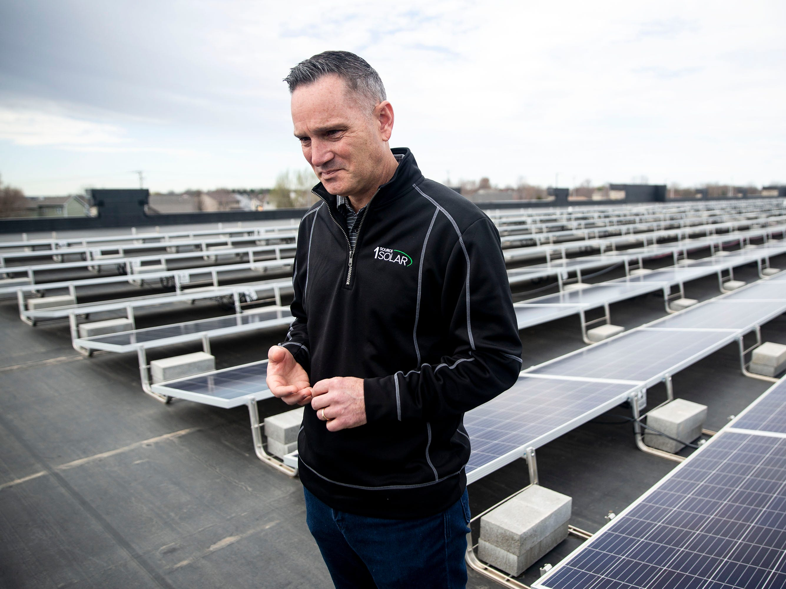Todd Miller, president of 1 Source Solar, stands near the solar panels that line the roof of 1 Source's building on Tuesday, April 9, 2019, in Ankeny.