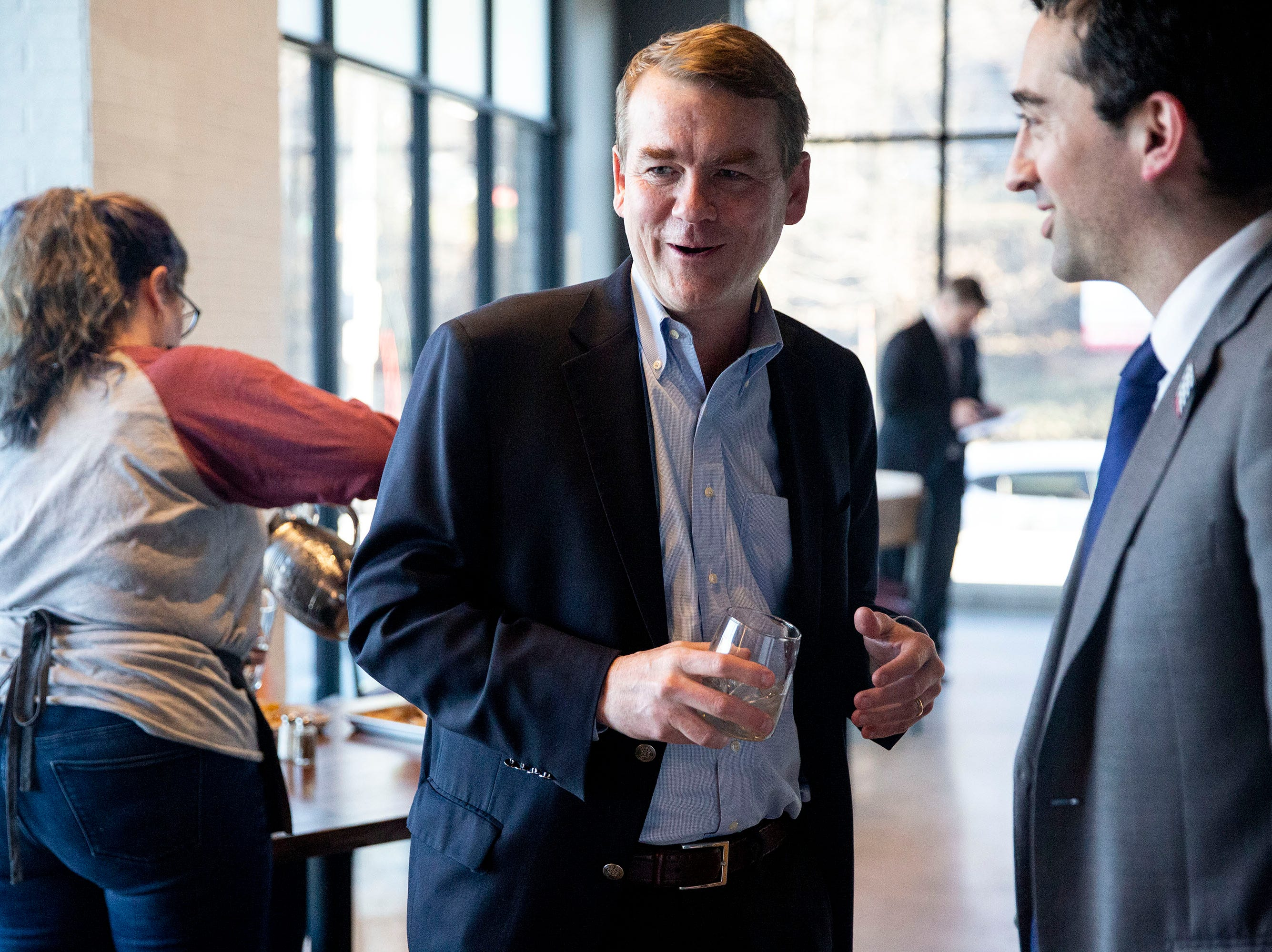 U.S. Sen. Michael Bennet, D-Colo, talks to Josh Mandelbaum, a member of the Des Moines City Council, before giving a speech and answering questions on Monday, April 8, 2019, during a meet and greet hosted by the Polk County Democrats at Teddy Maroon's in Des Moines.
