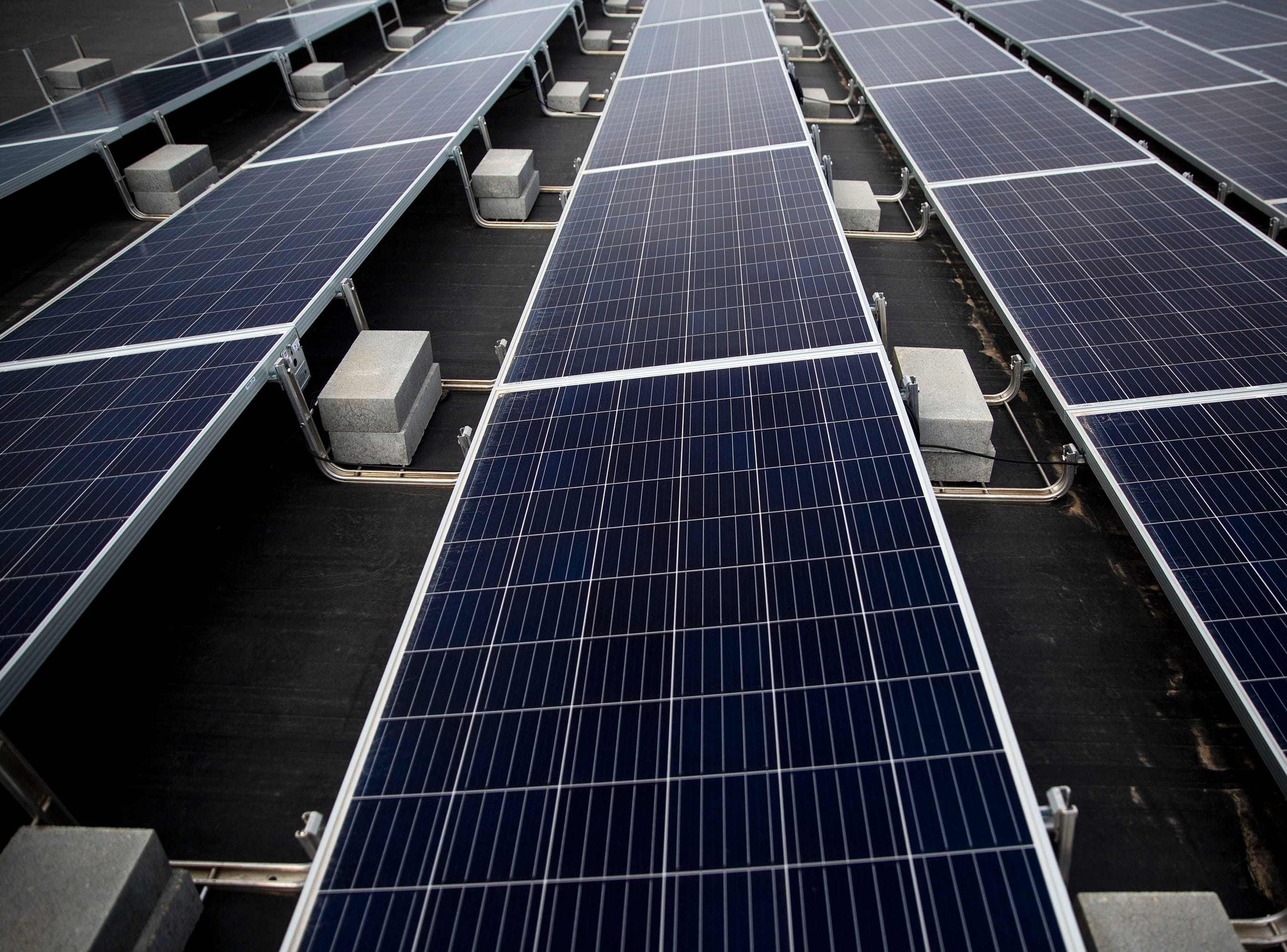 A set of solar panels absorbs sunlight on the roof of 1 Source Solar's building on Tuesday, April 9, 2019, in Ankeny. The solar array provides enough energy to eliminate the cost of electricity for all three of the businesses in the building.