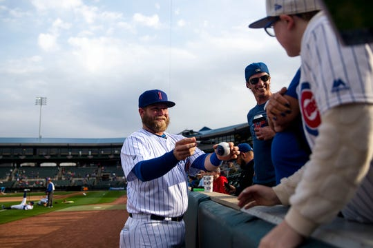 The Iowa Cubs' Taylor Davis autographs a baseball before the I-Cubs' home opener against the New Orleans Baby Cakes on Tuesday, April 9, 2019, at Principal Park in Des Moines.