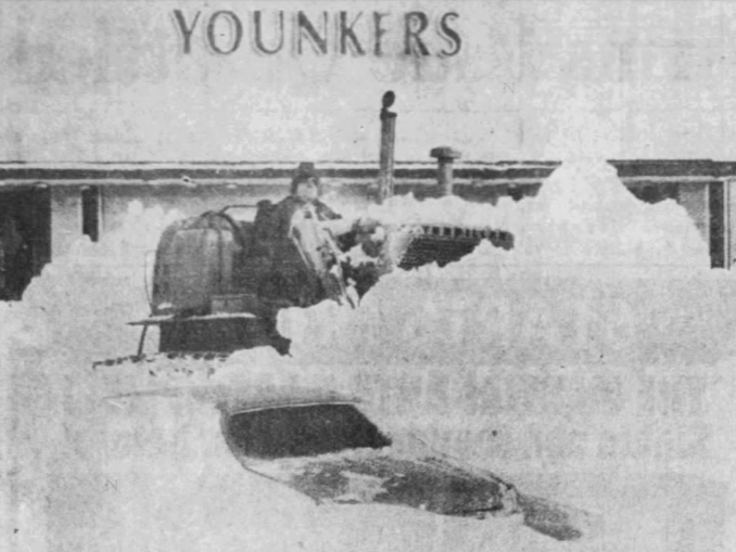 An automobile sits nearly covered by a huge snowdrift in the parking lot at Merle Hay Plaza as a bulldozer starts clearing the lot after a blizzard in April 1973.