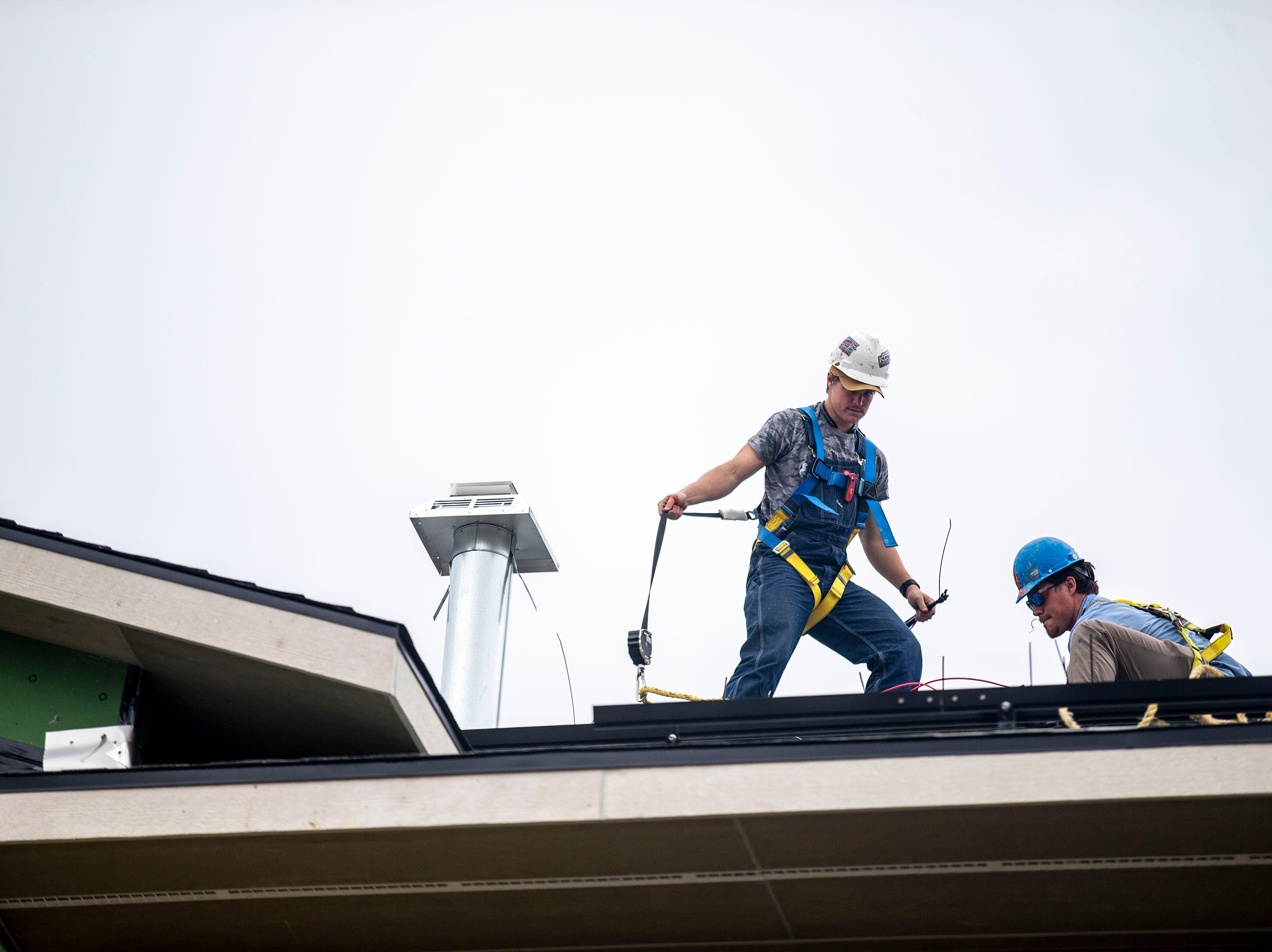 Nate Flynn and Jeremy Snead, working for 1 Source Solar, install a set of solar panels on the roof of a home under construction on Tuesday, April 9, 2019, in Waukee.