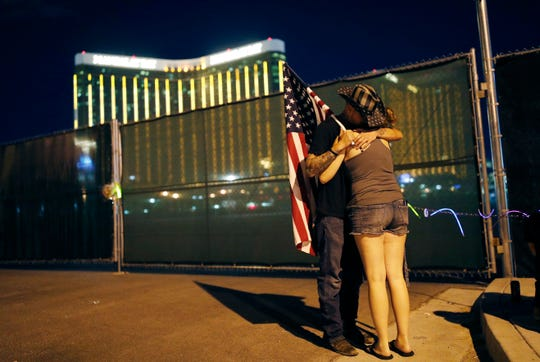 Kenneth Wright, left, embraces Cara Knoedler on the anniversary of the Oct. 1, 2017 mass shooting on Oct. 1, 2018, in Las Vegas. Behind them is the site of the shooting.