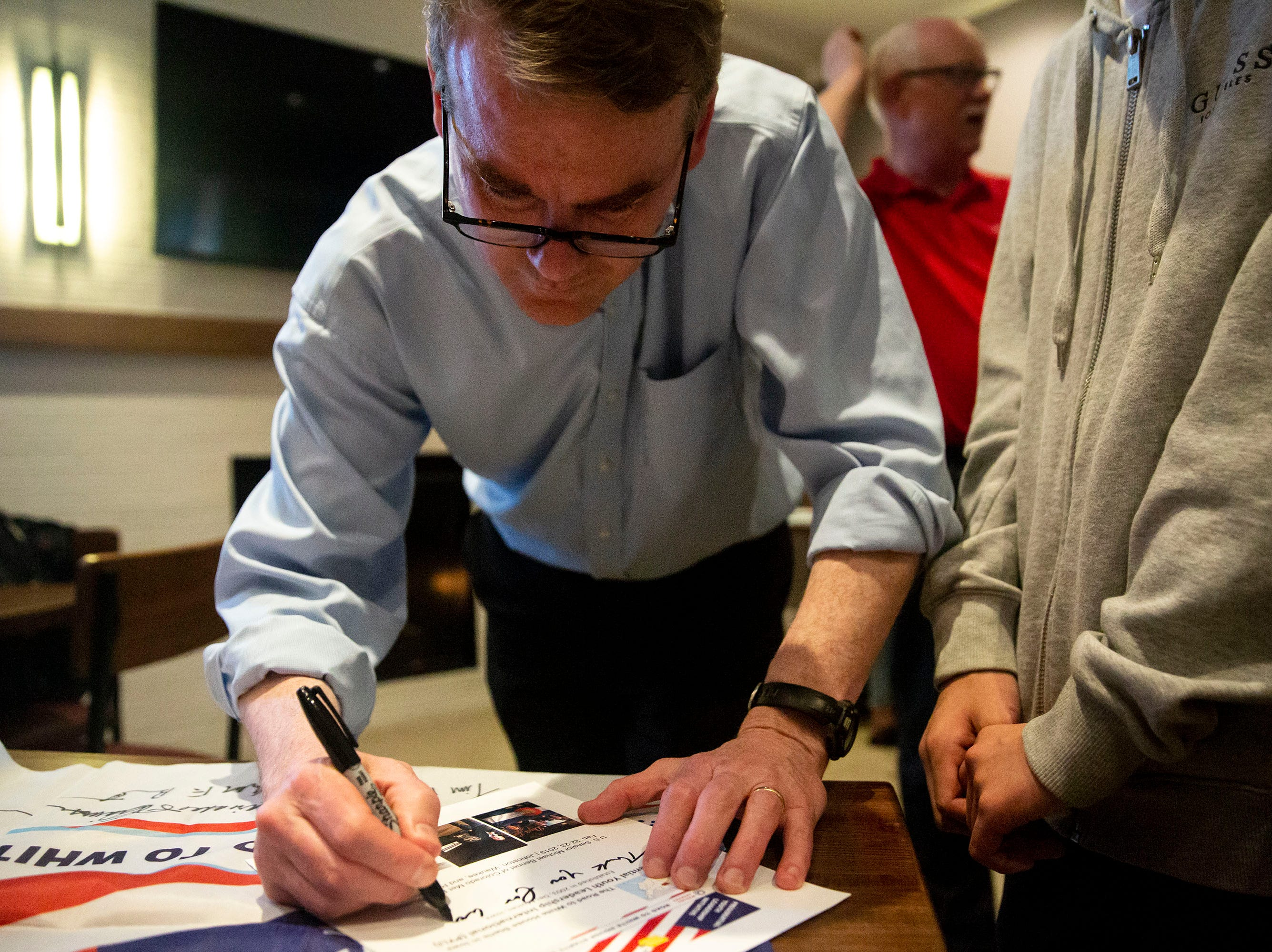 U.S. Sen. Michael Bennet, D-Colo, signs an autograph after giving a speech and answering questions on Monday, April 8, 2019, during a meet and greet hosted by the Polk County Democrats at Teddy Maroon's in Des Moines.