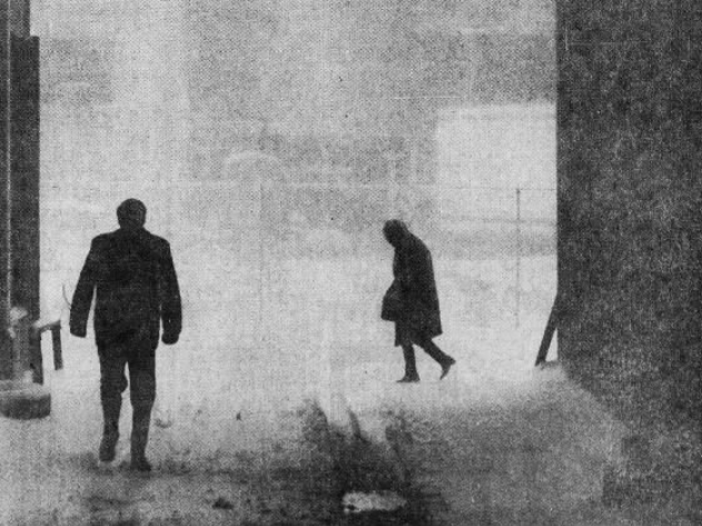 Pedestrians near 7th Street in downtown Des Moines, bundled up against the driving snow and blustery wind, walk with heads bowed into the elements during an April 1973 blizzard.