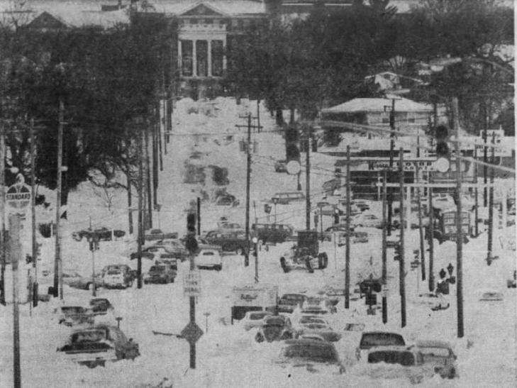 This view of stranded cars stuck and askew in the intersection of Harding Road and Euclid Avenue was typical of most of Des Moines after an April blizzard in 1973. This photo, looking west toward Veterans Hospital, shows a single road scraper working its way through the tangled intersection.