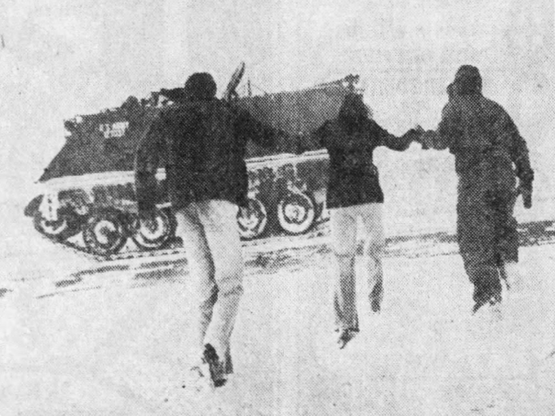 Iowa National Guardsmen head toward their armored pesonnel carrier near Interstate 80 east of Des Moines. The heavy military vehicles were used for emergency runs and to transport motorists stranded during the April 1973 blizzard.