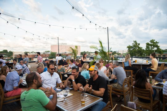 People converse on the third floor terrace of HopCat in Royal Oak, Mich. on Friday, July 20, 2018.