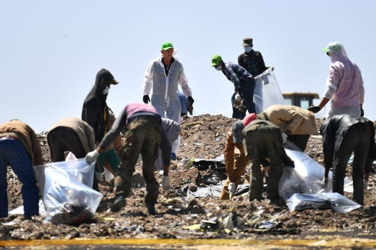 People work to search for belongings and  debris for forensic analysis at the  crash site of the Ethiopian Airlines operated Boeing 737 MAX aircraft in which their relatives perished among the 157 passengers and crew onboard, at Hama Quntushele village, near Bishoftu, in Oromia region, on March 15, 2019. -