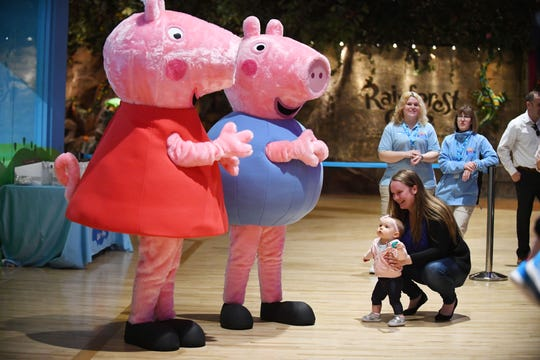 Christina Schafer with daughter Athena Schafer, 10 months, meet Peppa and George during the grand opening of the Peppa Pig World of Play on Tuesday at Great Lakes Crossing.
