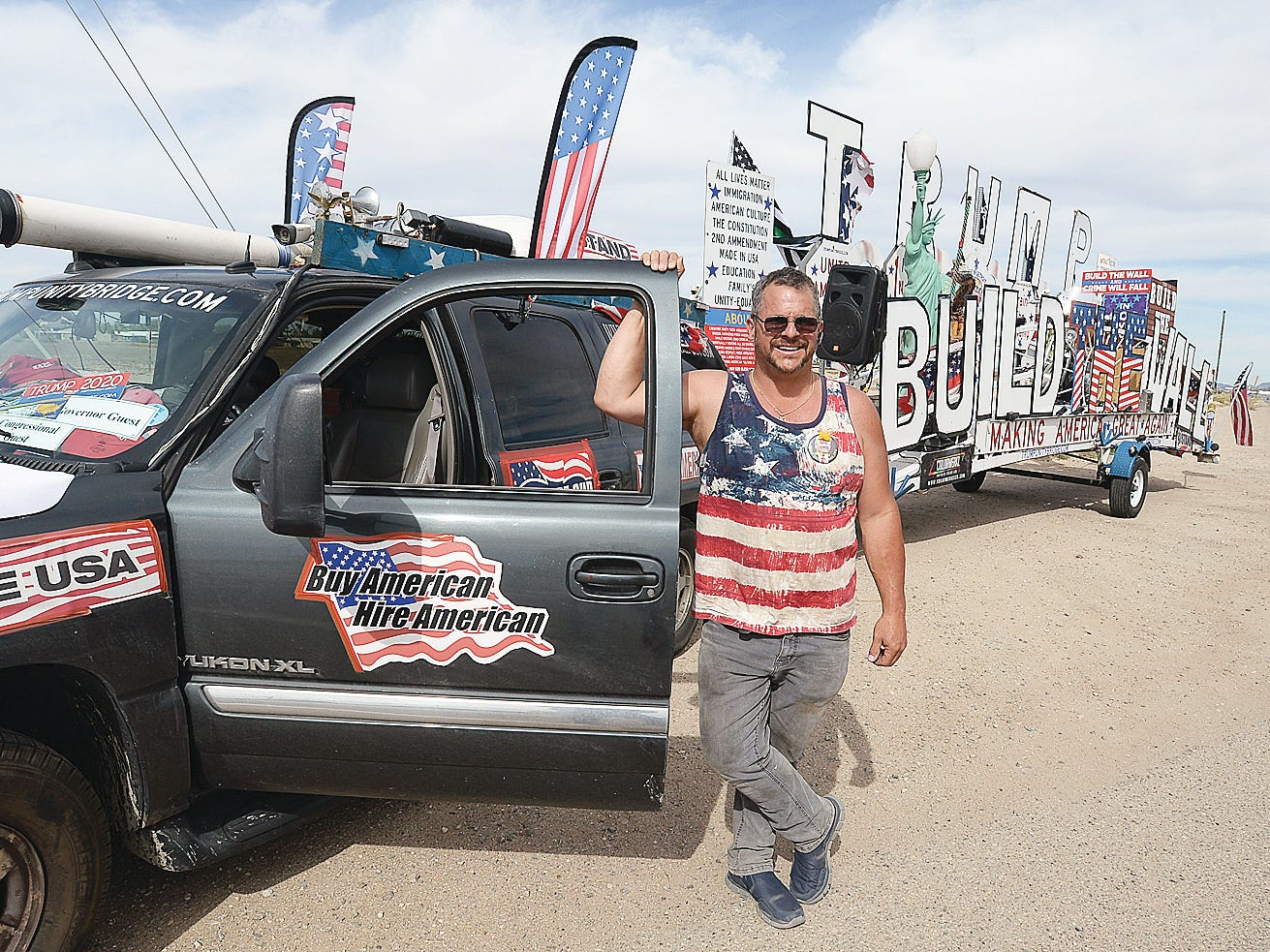 """Rob Cortis of Livonia, Mich., poses Monday, April 8, 2019, with his traveling """"Trump Unity Bridge"""" trailer display. After arriving in Yuma, Ariz., he parked across the street from the U.S. Border Patrol Yuma Sector Headquarters."""