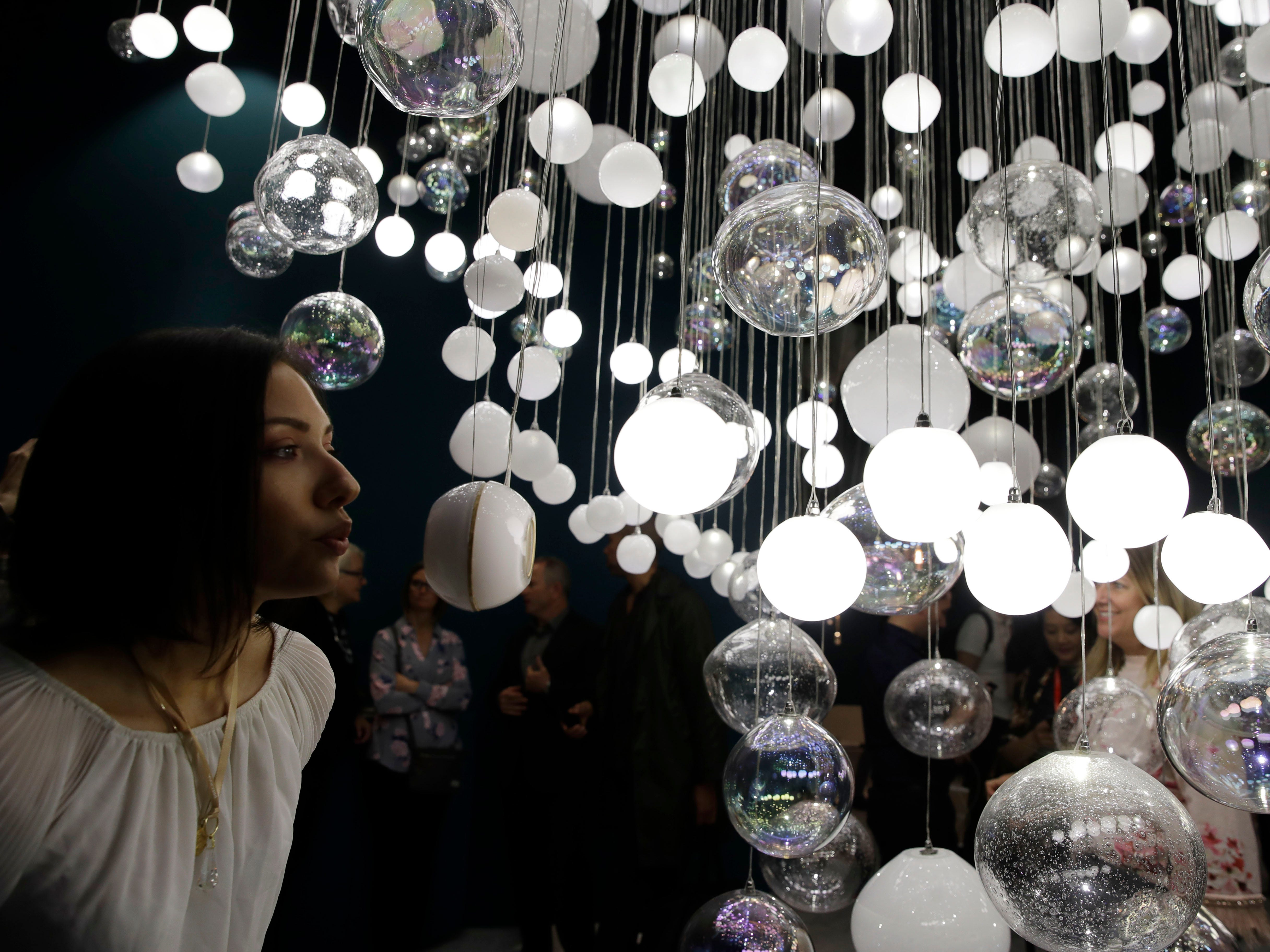 An assistant blows into a crystal bubble of the 'Breath of Light' to turn on light bulbs, creation for Preciosa by creative director Michael Vasku, displayed at the Salone del Mobile Furniture Fair, in Rho, near Milan, Italy, Tuesday, April 9, 2019. The Salone del Mobile fair takes place in various locations across Milan from April 9 through 14, 2019.